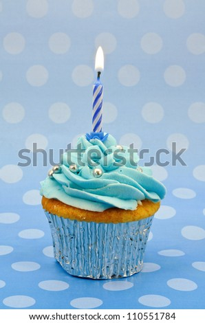 A home baked baby blue cup cake with a single lit candle to celebrate a first birthday or other anniversary - stock photo
