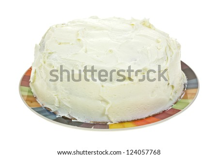 A home baked layered frosted cake on a colorful plate. - stock photo