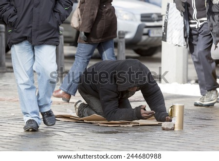 A homeless begger is begging on a busy street in the center of Sofia.  - stock photo