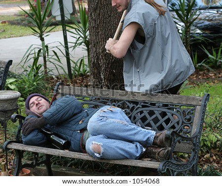 A homeless man sleeping on a park bench and a young man about to beat him with a bat. - stock photo