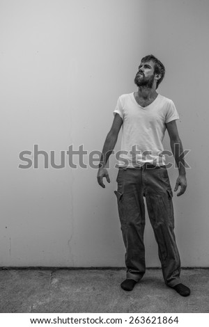 A homeless man stands on the sidewalk and looks towards the sky with light shinning down on the wall behind, with copy space - stock photo
