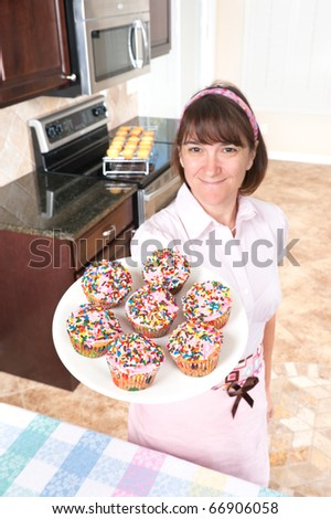 A homemaker shows off her decorated cupcakes with pink icing and candy sprinkles.  Focus is on the cupcakes. - stock photo