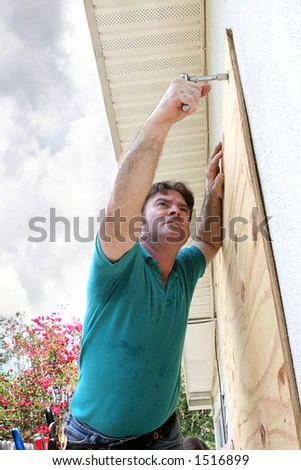 A homeowner covering his windows with plywood in preparation for a hurricane. - stock photo