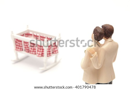 A homosexual couple looking at an empty crib - stock photo