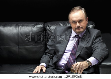 A horizontal image of a man wearing formal suit sitting on a black leather sofa