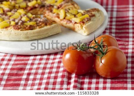 A horizontal image of hawaiian pizza and whole ripe tomato on a checkered table cloth - stock photo