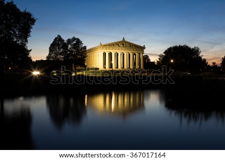 A Horizontal image of the Parthenon in Nashville, Tennessee, at night and it's reflection in a pond.  - stock photo