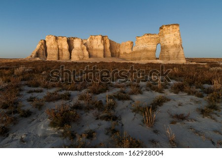 A horizontal landscape photography image of Monument Rocks in Kansas before sunset.  They are also known as Chalk Pyramids.  - stock photo