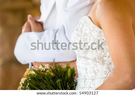 A horizontal photo of a caucasian bride and groom holding hands during a wedding reception