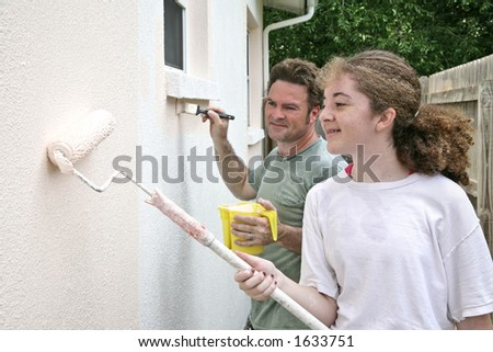 A horizontal view of a father and daughter painting their house together. - stock photo