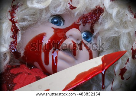 A horrorifying scene of a childs doll covered in a bloody mess.