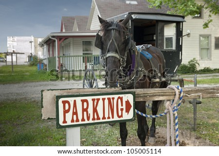 A horse and buggy are tied up to a parking sign beside a country house in a rural community - stock photo