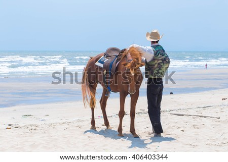 A horse and stableman on the beach