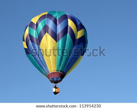 A hot air balloon in the bright blue sky - stock photo