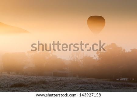 A hot air balloon rises thru the fog just as the sun rises on a cold winter's morning in the Yarra Valley, Victoria, Australia - stock photo