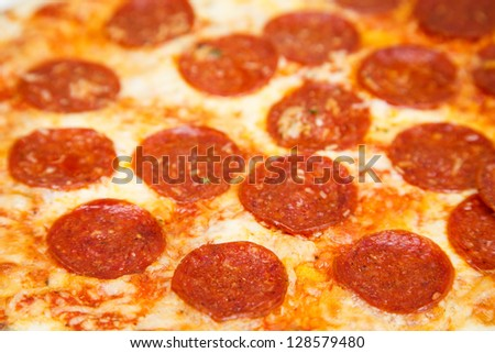 A hot and cheesy pizza with pepperoni, ready to eat - stock photo