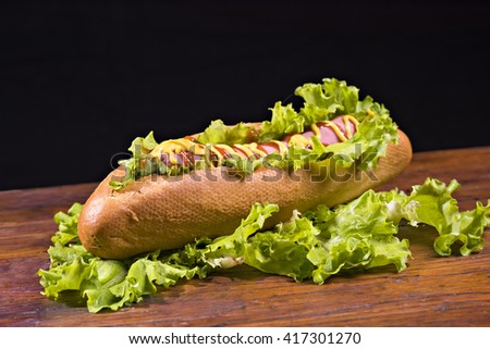 A hot dog is decorated with lettuce on a wooden table and watered mustard - stock photo
