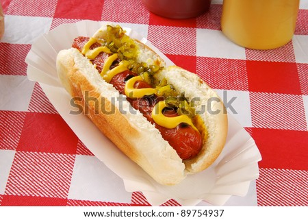 A hot dog with relish on a picnic table - stock photo