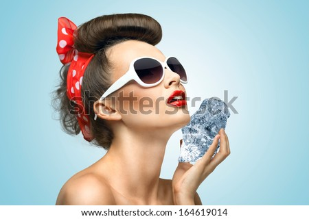A hot photo of beauty touching her face with the piece of ice holding in her hands.