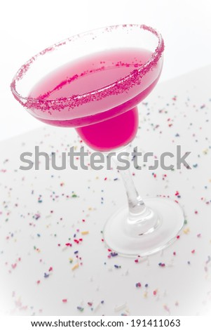 A hot pink margarita in a margarita glass with pink sugar on the rim; festive sprinkles surround it