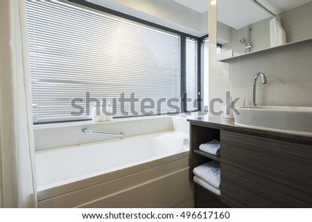 A hotel bathroom with blind, sink(basin), bathtub(bath), lighting front view at the day in seoul, south korea.