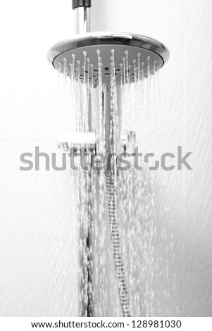 A hotel shower head flowing with water - stock photo