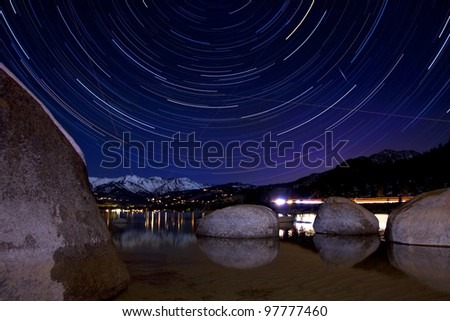 A 2-hour star trail photo taken at Sand Harbor, Lake Tahoe. - stock photo