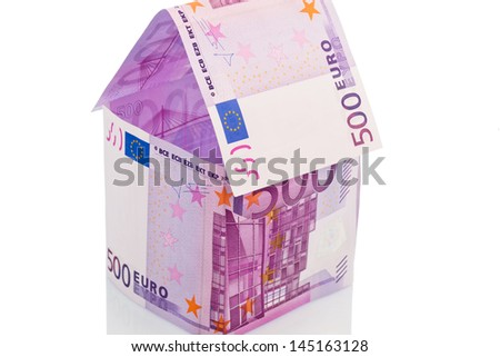 a house built with money euro appear on a white background. building society, building houses and buying a house. - stock photo