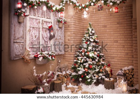 A house  decorated with lanterns, Christmas tree branches,  garland and Christmas lights studio shot. Winter yard.  Image toned. - stock photo