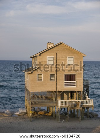 A house in Nags Head on the Outer Banks of North Carolina. The beach has eroded away from around the base of the home and sand bags have been placed to try to protect it from collapsing. - stock photo