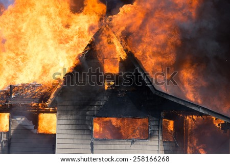 A house is consumed by flames in a blazing fire. - stock photo
