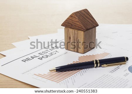 A house(made in wood block) with pen and graph paper(document) on the wood office desk(table) behind white blind.