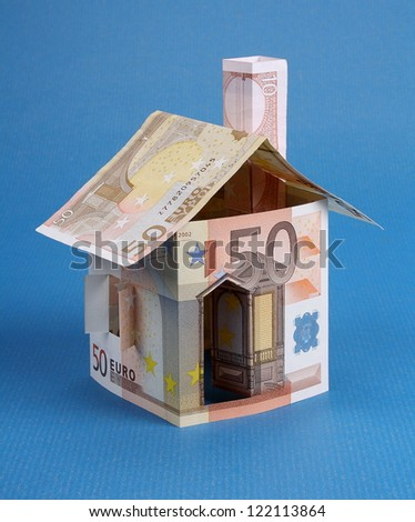 A house made of euro notes on a blue background - stock photo