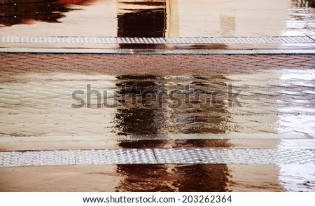A house reflected in the puddle on brown pavement in rainy day. Paris, France. Blur. Selected focus on the wet  tile pavement. - stock photo