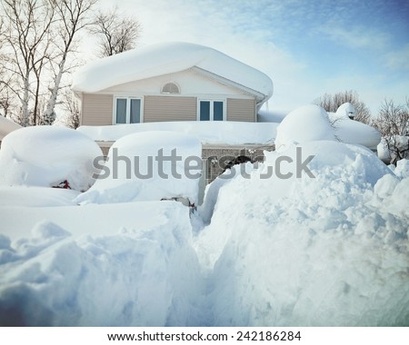 A house, roof and cars are covered with deep white snow in western new york for a weather or blizzard concept. - stock photo