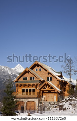 A house typical of west coast architecture, sits against the backdrop of the Tantalus Range in Squamish, British Columbia.
