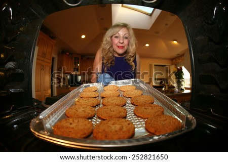 A house wife bakes cookies for her loving family. Shot from Inside the Oven Out for a Unique View not often seen. Focus is on the cookies with the woman slightly out of focus. Everyone LOVES Cookies - stock photo