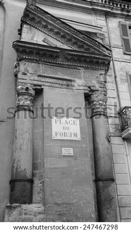 A house with Roman portico and columns at Forum square (Place du Forum) in Arles (Provence, France). Aged photo. Black and white. - stock photo