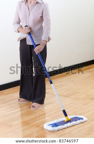 A housewife cleaning wooden floor by mop