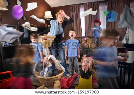 A housewife is stressed and tried trying to clean the house while wild children are running around making a mess for a discipline or parenting concept. - stock photo