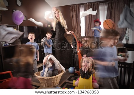 A housewife is wearing a glamorous beautiful dress and cleaning the house while wild children are running around making a mess. - stock photo