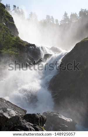 a huge and wild waterfall with trees surrounding it