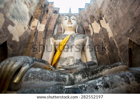A huge antique Buddha in the old city in Thailand