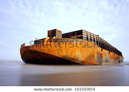 a huge barge stranded at the beach - stock photo