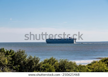A huge commercial tanker sailing close to shore - stock photo
