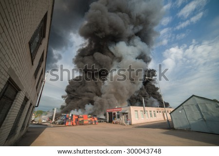 A Huge fire n the industrial area of the city. Buildings and cars in the fire. Open fire and black smoke going up to the sky. Picture taken with wide angle lens, representing necessity of insurance.  - stock photo