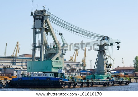 a huge floating crane by a river wharf