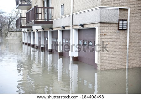 A huge flood near an apartment with many brown garages on a cloudy day. - stock photo