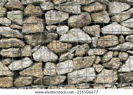 A huge Gabion Wall used as a fence on a slope. Colorful stones ideal for various kinds of backgrounds.