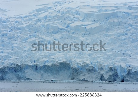A huge glacier in Antarctica, more than hundred meters high. Its core shows the deep cobalt blue colour of centuries-old ice.  - stock photo